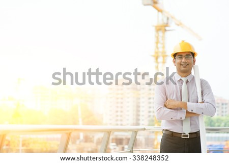 Portrait of Asian Indian male site contractor engineer with hard hat holding blue print paper looking at camera and smiling at construction site, crane with golden sunlight at the background. - stock photo
