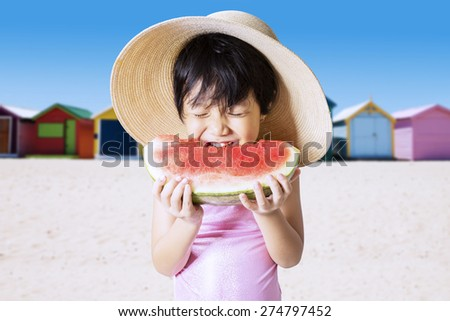 Portrait of asian little girl enjoy a fresh watermelon on the seaside while wearing swimwear and hat - stock photo