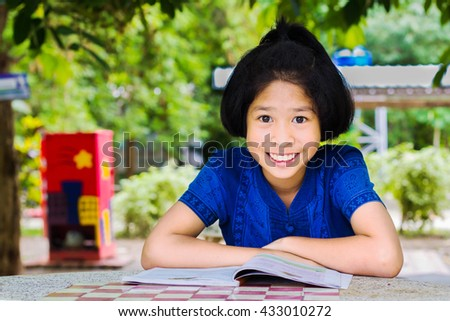 Portrait of Asian little girl reading a book in park