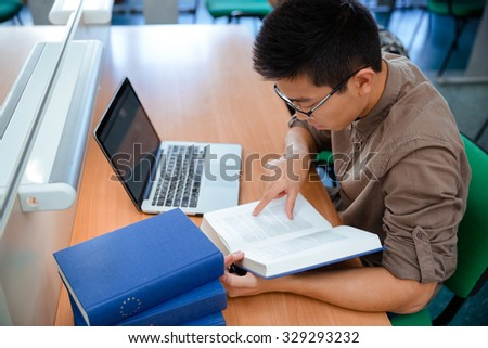 Portrait of asian male student reading book in university - stock photo