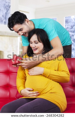 Portrait of asian man giving a gift to his expectant wife on the sofa at home  - stock photo