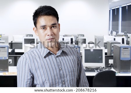 Portrait of asian man in office looking at camera - stock photo