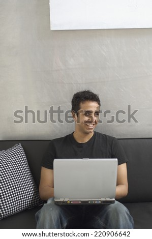Portrait of Asian man typing on laptop - stock photo