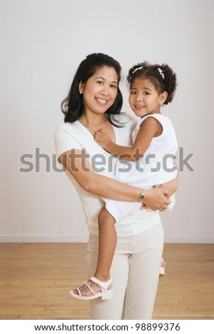 Portrait of Asian mother holding daughter - stock photo