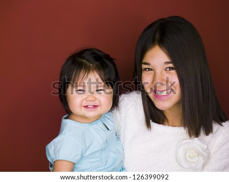 Portrait of Asian sisters smiling