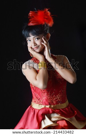 portrait of asian teenage girl dressing glamorous red gold on black background
