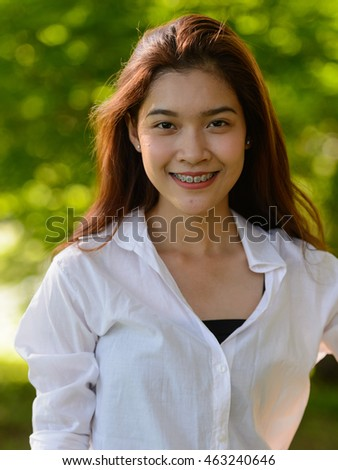 Portrait of Asian teenager girl smiling outdoors in park