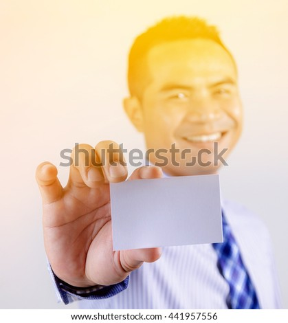 Portrait of asian Thai business man smile and showing blank white business card selective focus shallow depth of field with sunray effect - stock photo