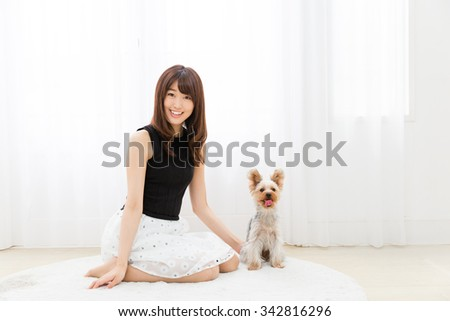portrait of asian woman and dog in the room - stock photo