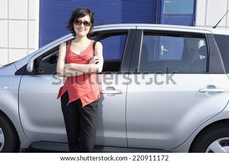Portrait of Asian woman leaning against car - stock photo