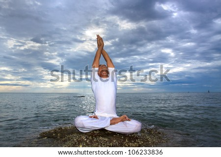 Portrait of Asian young man doing yoga exercise on stone with cloudy sky and ocean, Thailand