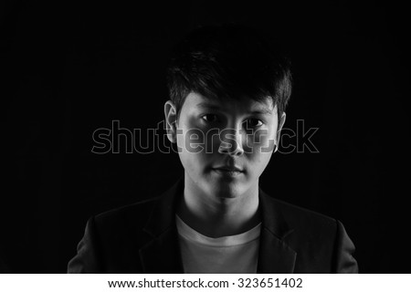 Portrait of Asian young man on black background