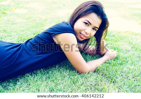 Portrait of asian. Young smiling woman lying on the grass. - stock photo