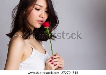 Portrait of asian young woman with red rose flower - stock photo