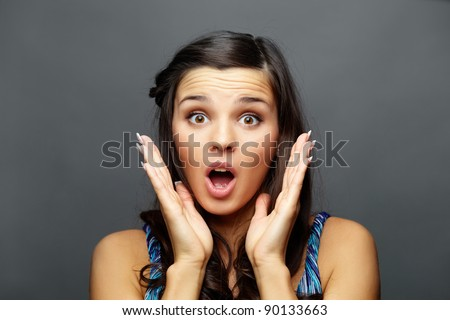 Portrait of astonished brunette looking at camera - stock photo