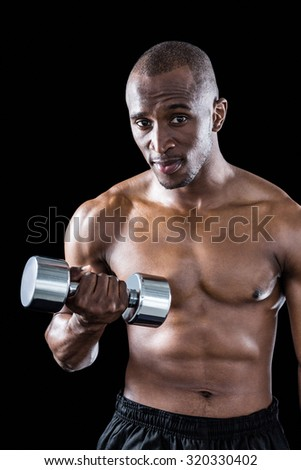 Portrait of athlete exercising with dumbbell standing against black background
