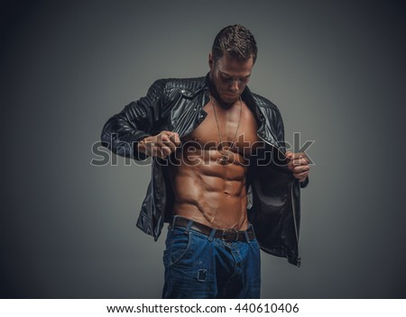 Portrait of athletic male in a jeans and leather jacket on a grey background.