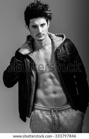 Portrait of athletic man wearing hoodie jacket. Studio shot - stock photo