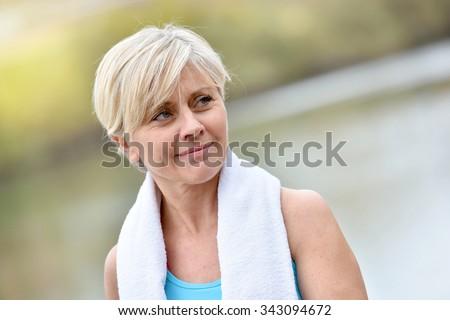 Portrait of athletic senior woman with towel around neck - stock photo