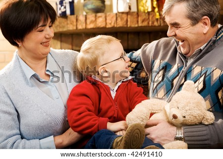 Portrait of attentive boy looking at grandfather while the latter telling something - stock photo