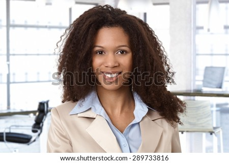 Portrait of attractive african woman at office, looking at camera, smiling. - stock photo