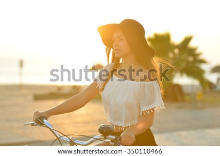Portrait of attractive amazed brunette with open mouth wearing black hat and white top having fun riding her bicycle along embankment  - stock photo