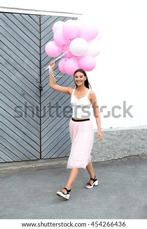 Portrait of attractive and cheerful girl walking with air balloons and looking at camera - stock photo