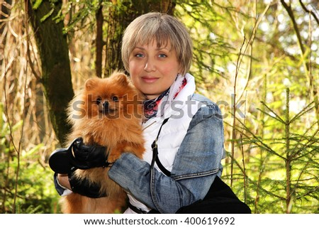 Portrait of attractive and serene mature woman. Lovely middle-aged blond woman. Beautiful happy woman with pomeranian dog. Woman in forest - stock photo