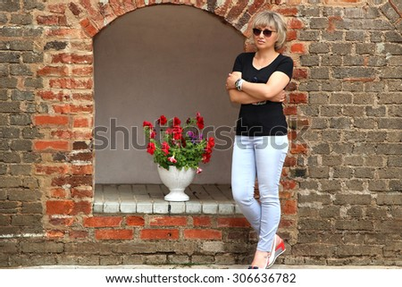 Portrait of attractive and serene mature woman. Lovely middle-aged blond woman. Beautiful woman in black shirt standing on the old street. - stock photo