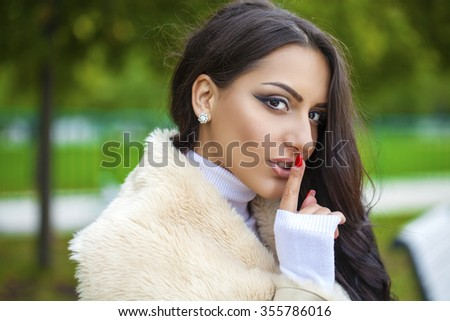 Portrait of attractive arabic girl with finger on lips, concept of student show quiet, silence, secret gesture, young pretty brunette woman in autumn park - stock photo