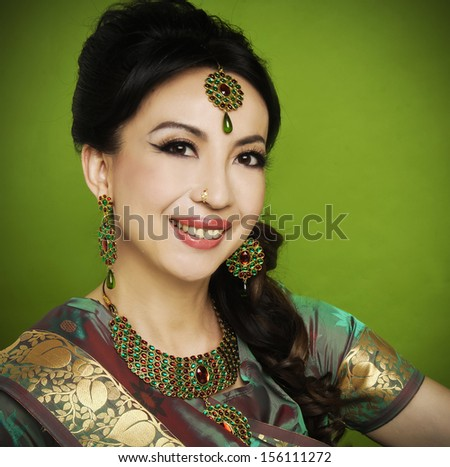 portrait of Attractive asian woman in traditional clothing with bridal makeup and jewelry-green background - stock photo