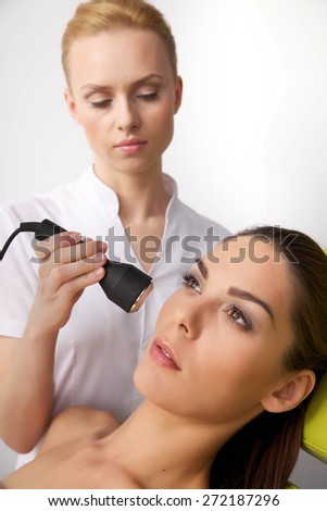 Portrait of attractive beautiful young adult brunette woman having a stimulating facial treatment from a therapist on the table in professional clinic spa - stock photo