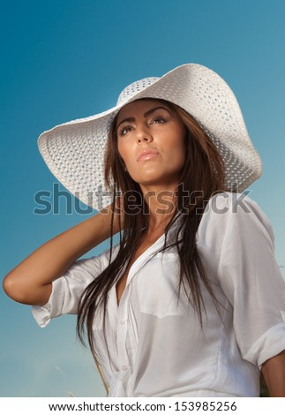 Portrait of attractive beautiful young woman in summer cap closeup, against blue sky.Woman with sun hat