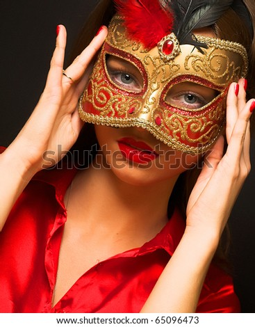Portrait of attractive beautiful young woman wearing red cold  carnival mask - stock photo
