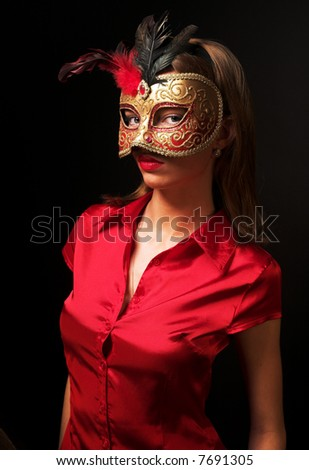 Portrait of attractive beautiful young woman wearing red cold  carnival mask