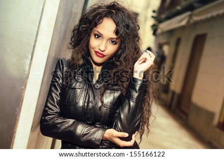 Portrait of attractive black woman in urban background wearing leather jacket - stock photo