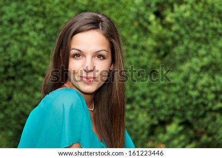 Portrait of attractive brunette girl, smiling and looking to the camera.