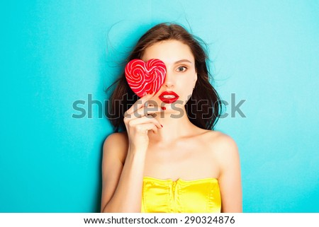 Portrait of attractive brunette girl with candy in his hands in the studio on a blue background, the concept of beauty - stock photo