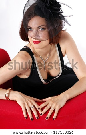 portrait of attractive brunette sitting in a red chair