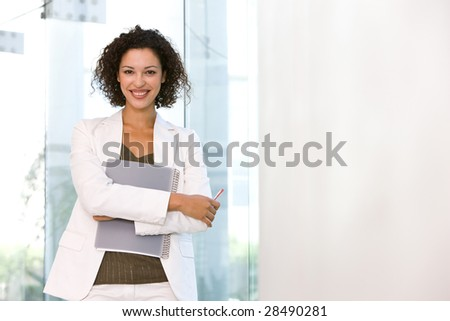 Portrait of attractive business woman holding folder - stock photo