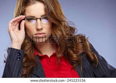 portrait of attractive business woman isolated on grey studio with glasses