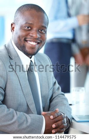 Portrait of attractive businessman looking at camera in working environment
