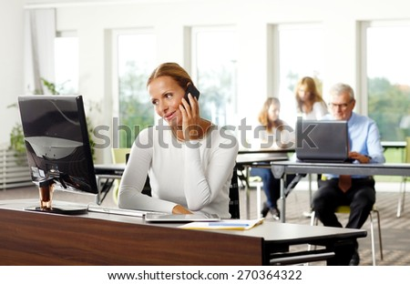 Portrait of attractive businesswoman sitting at office in front of computer while making call. Business person working at office.  - stock photo
