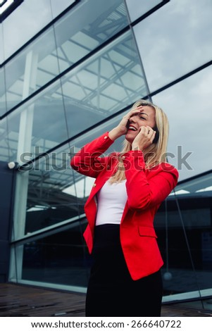 Portrait of attractive businesswoman throwing her head back with one hand on her face in laughter having conversation on cell phone, woman laughing during talking to friend on smart phone, filter - stock photo