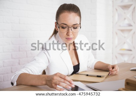 Portrait of attractive businesswoman using smartphone at wooden office table with paperwork