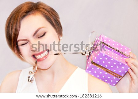 Portrait of attractive caucasian girl with gift box. Caucasian beautiful young girl in her 20s. Strong expressive emotion. Grey background, indoor.  - stock photo