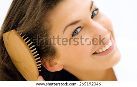 portrait of attractive caucasian smiling woman brunette brushing her hair - stock photo