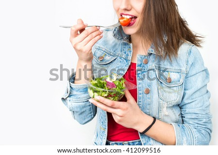 Portrait of attractive caucasian smiling woman eating salad - stock photo