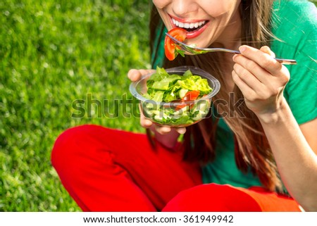 Portrait of attractive caucasian smiling woman eating salad, focus on hand - stock photo