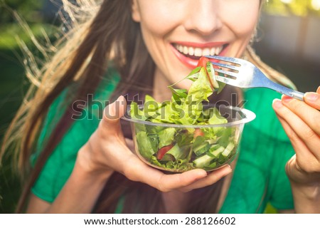 Portrait of attractive caucasian smiling woman eating salad, focus on hand and fork. soft, backlight
